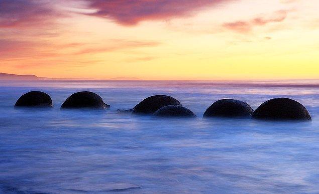 10. Yeni Zelanda'daki yuvarlak kayalar: Çamurtaşını çevreleyen kıyı erozyonu sonucu denizin içinde ve sahilde oluşan yuvarlak kayalar.