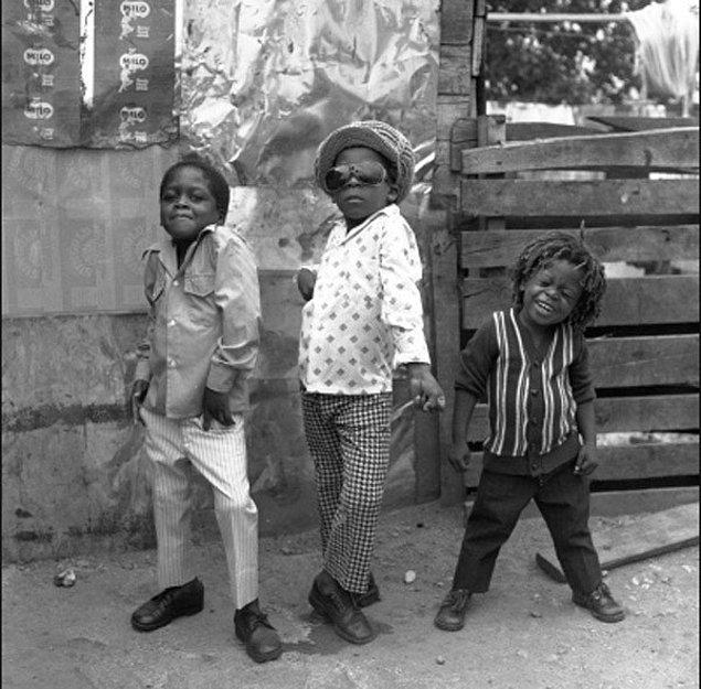 22. Jamaika sokaklarında kameraya poz veren 3 çocuk
