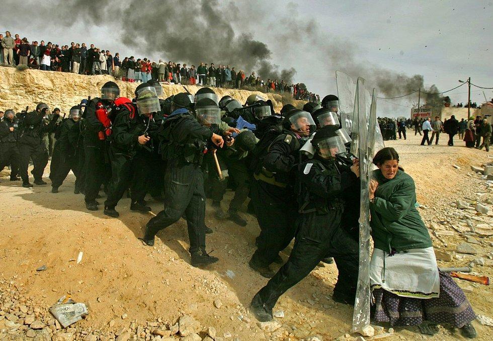2006 yılında Batı Şeria'da çekilen fotoğrafta Israilli bir kadının İsrail güvenlik güçlerine direnmesini görüyoruz. Oded Balilty tarafından çekilen fotoğraf, İsrail'in Ramallah'a komşu olan bir yerleşim bölgesini boşaltma kararı vermesi sonucu, evini terk etmek istemeyen İsraillilerin polise karşı gelmesini gösteriyor.
