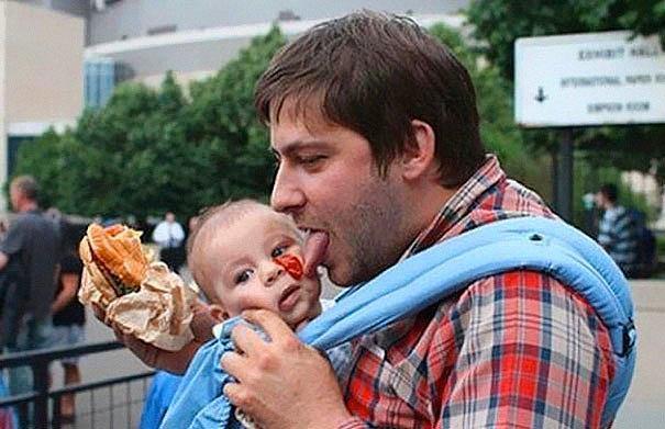 Отец пытается слизать кетчуп с лица своего сына.