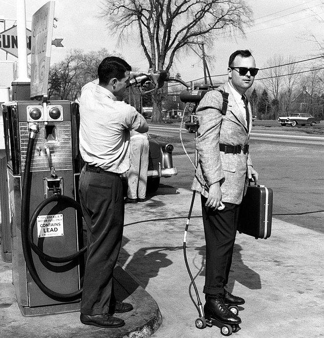 7. Sırtında taşıdığı motorlu tekerlekli paten sistemine benzin dolduran bir satıcı.