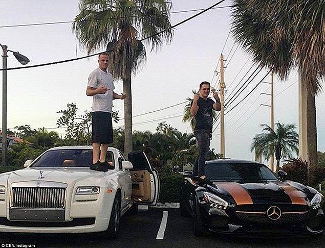 Pahalı arabalarının üstüne çıkarak poz veren iki adam