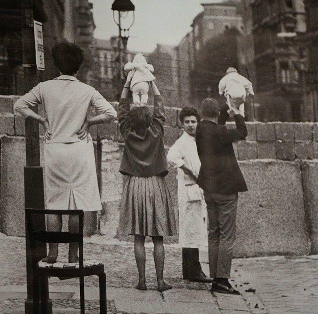 1. Batı Berlin'de bulunan bir aile Doğu Berlin'de bulunan büyükbaba ve büyükannesine aradaki duvar üzerinden çocuklarını gösteriyor, 9 Mayıs 1961.