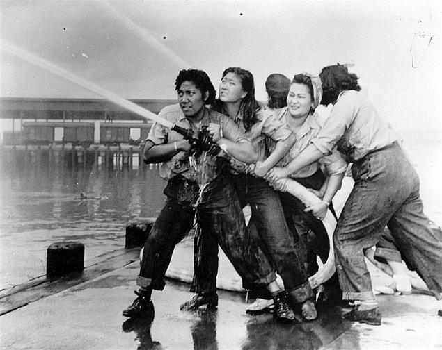 19. Japonların saldırısı sonrası ABD deniz üssü Pearl Harbor'da kadın itfaiyeciler tazyikli hortumu tutmaya çalışırken, 1941.