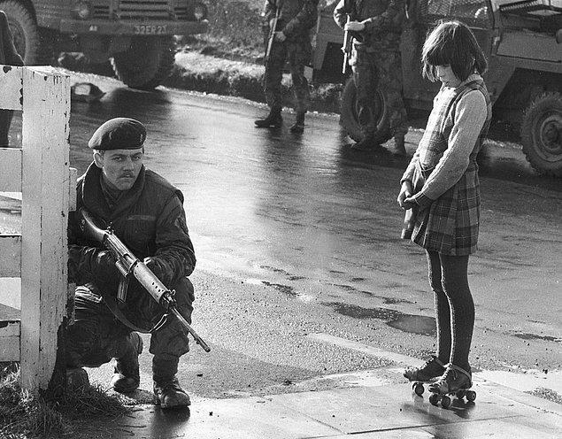 27. Kargaşa zamanlarında paten giymiş İrlandalı bir kız Britanya askerine bakarken, Kuzey İrlanda, 1970 sıraları.