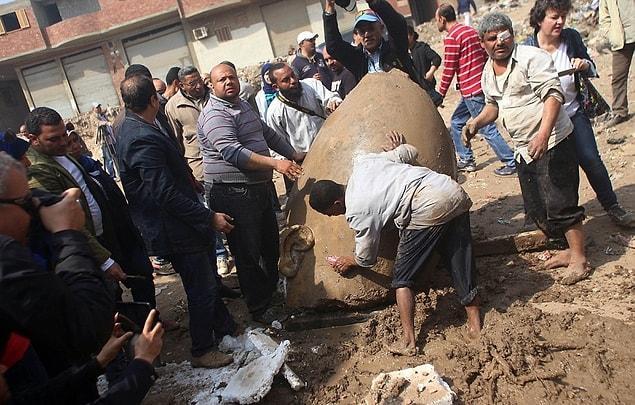"""Mısır Antikite Bakanı Khaled al-Anani açıklamalarında: """"Heykelin göğüs kısmını çıkardık ve şimdi de kafayı bulduk. Sonrasında sağ kulak, taç ve sağ gözün bir kısmı ortaya çıktı."""" dedi"""