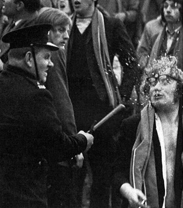 22. Polisin elindeki cop ile grev yapanlardan birinin gözlüklerini parçaladığı an, 1960'lar.