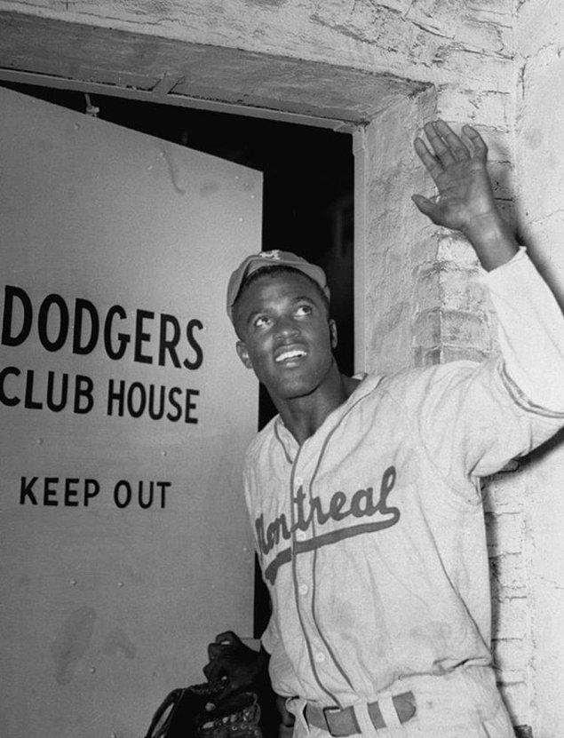 6. Major Lig'de oynayan ilk siyahi beyzbolcu olan Jackie Robinson, Brooklyn Dodgers'ın kulüp binasına girerken, 10 Nisan 1947.