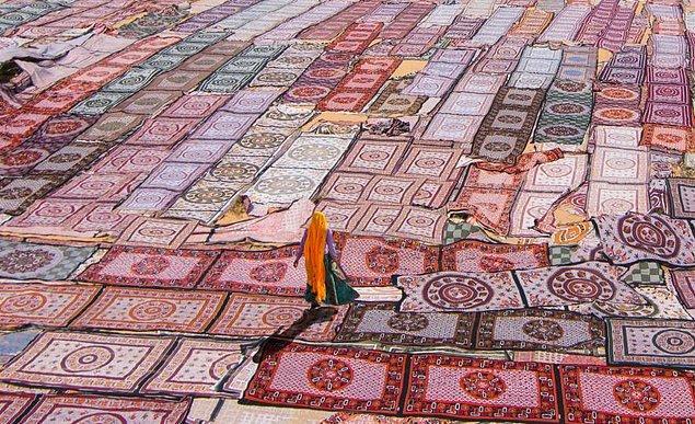 10. Hindistan'da kurumaya bırakılmış örtülerin üzerinden yürüyüp giden bir kadın.