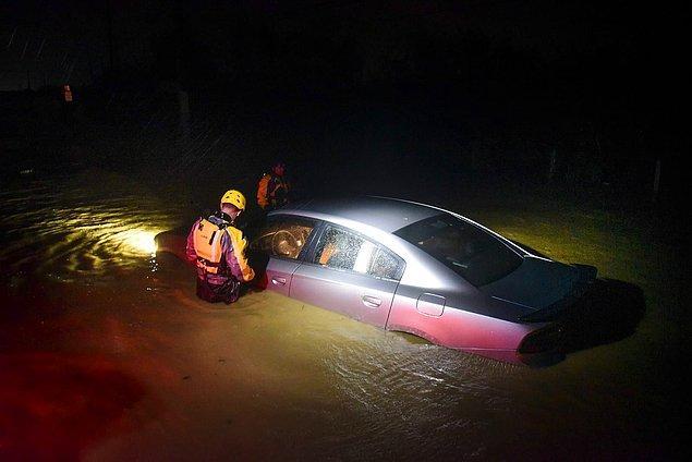11. Porto Riko'da belediyenin acil durum ekipleri kasırgada sular altında kalmış bir aracın içini inceliyor.