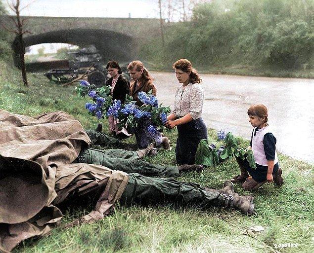 2. ABD ordusu tarafından çalışma kampından kurtarılmalarının ardından üç Rus kadın ve küçük bir kız, 4 ölü ABD askerinin ayak ucuna çiçekler bırakırken, Hilden, Almanya, 18 Nisan 1945.