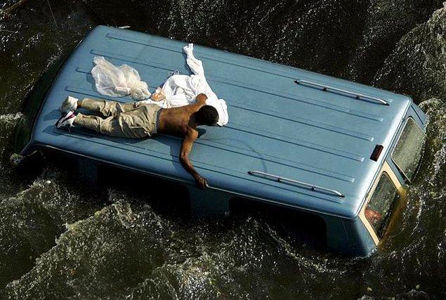 8. Yine bir kasırga sonrası yükselen suların arasında kalmış, minibüsün tepesinde çaresizce yardım bekleyen adam.