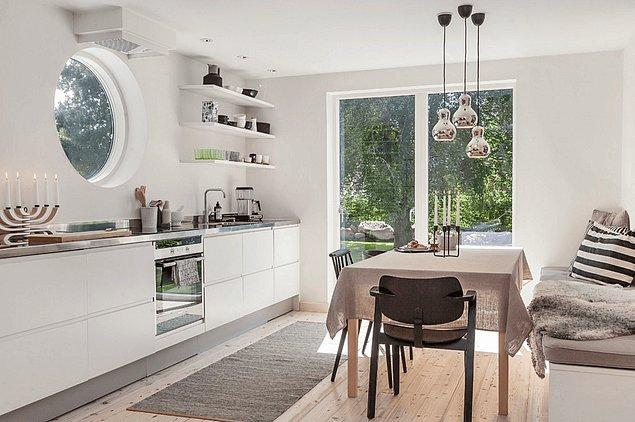 5. Bu minimalist mutfak gözlerinizi bahçeye çevirmek için yaratıcı çözümler bulmuş, özellikle bu yuvarlak pencereyle...