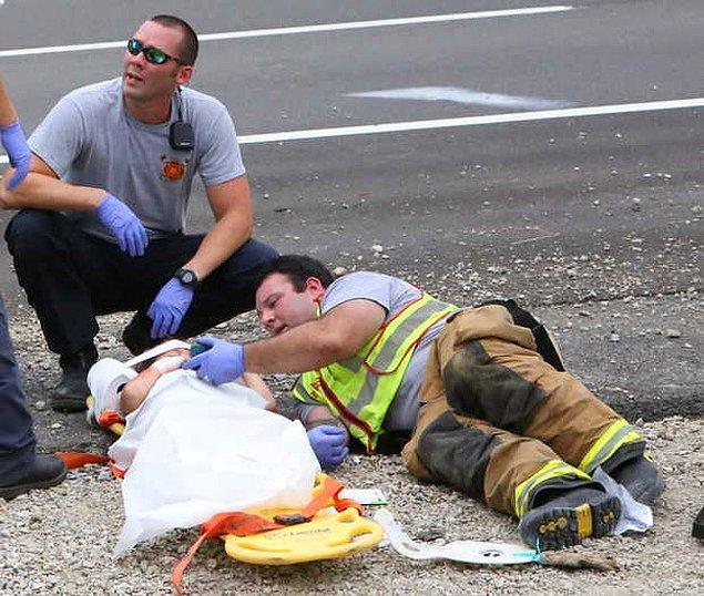 3. Yerel bir itfaiyeci, yangından korkan çocuğu telefonundan bir şeyler izleterek sakinleştiriyor...