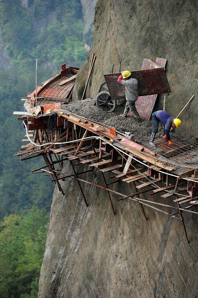 1. Turistleri çekebilmek için dağın kenarında yeni bir yol yapmaya çalışan Çinli işçiler.