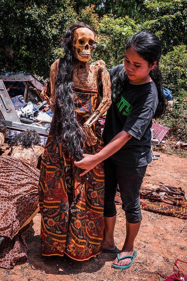 Uzun saçlı bir kadının akrabası tarafından saçlarına bakım yapılıyor.