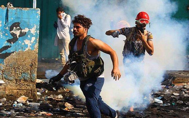 Protestocular, polis güçlerinin fırlattığı göz yaşartıcı gazlardan kaçıyor.