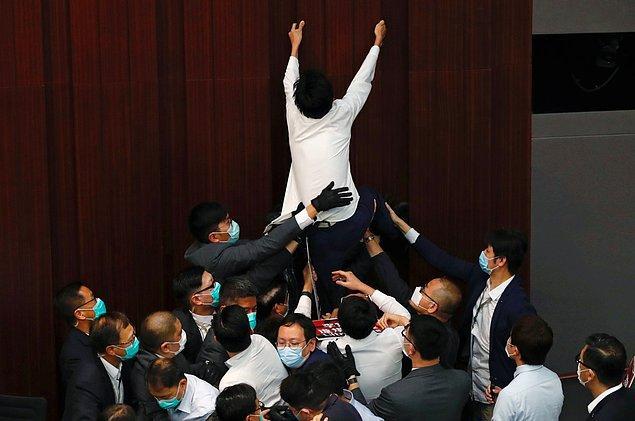 Milletvekili Eddie Chu Hoi-dick ise komite başkanlığı koltuğuna ulaşmak için duvara tırmanmaya çalışırken 4 güvenlik görevlisi tarafından salon dışına çıkarıldı.