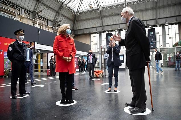 Paris'teki 'Gare de l'Est Tren İstasyonu'nda sosyal mesafe belirteçleri üzerinde duran bürokratlar.
