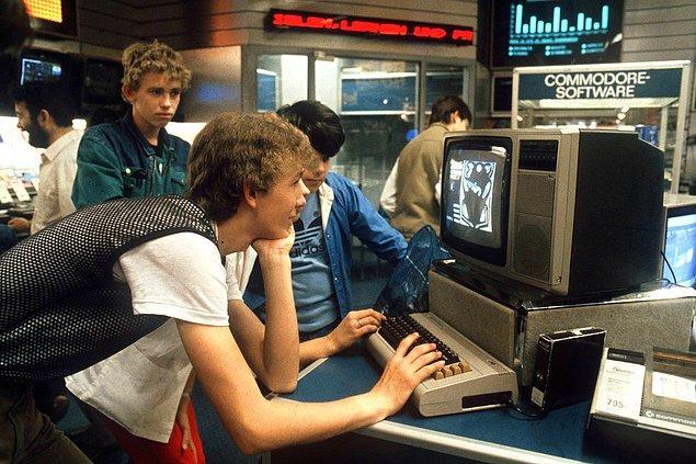 4. Almanya Nuremberg'de bir grup genç teknoloji mağazasında Commodore bilgisayar ile oynuyor. -1984